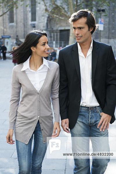 Ein Paar geht und redet zusammen im Freien.