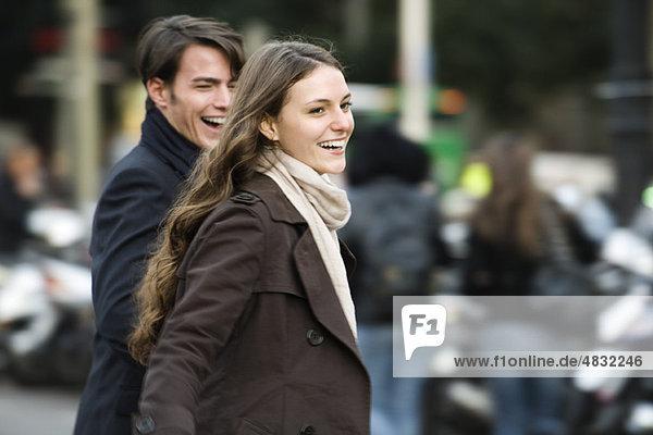 Junges Paar lacht und geht gemeinsam im Freien spazieren