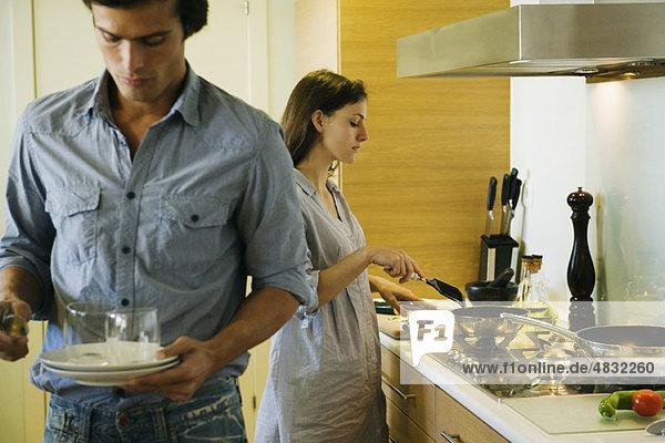 Paar in der Küche  Frau kocht  während der Mann den Tisch deckt.
