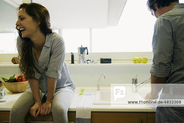 Couple in kitchen  man washing dishes  woman sitting on counter laughing