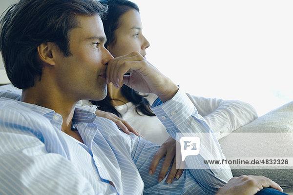 Ein Paar sitzt zusammen  beide schauen in Gedanken weg.