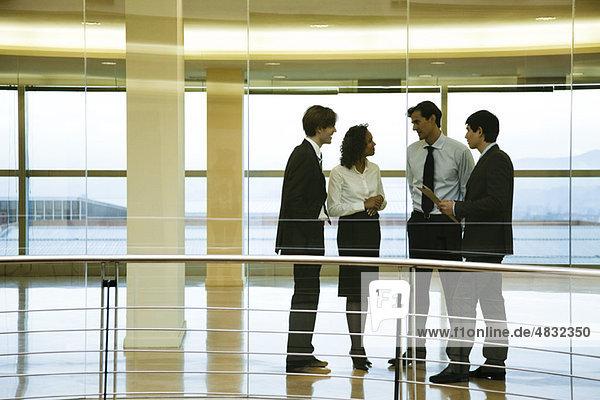 Gruppe von Führungskräften im Gespräch im Korridor