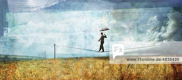Mann mit Regenschirm balanciert auf Überlandleitung