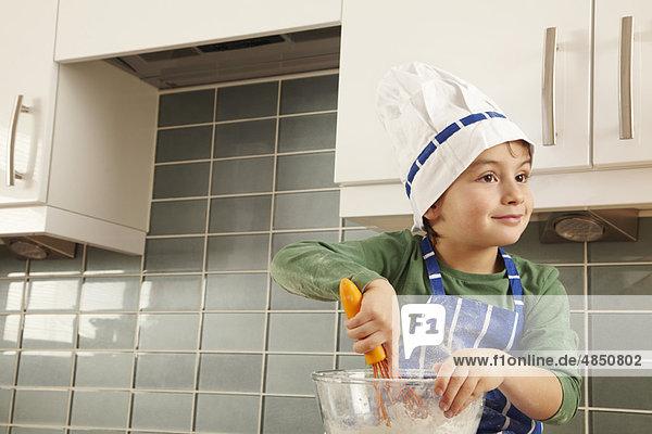 Kleiner Junge mit Rührschüssel in der Küche