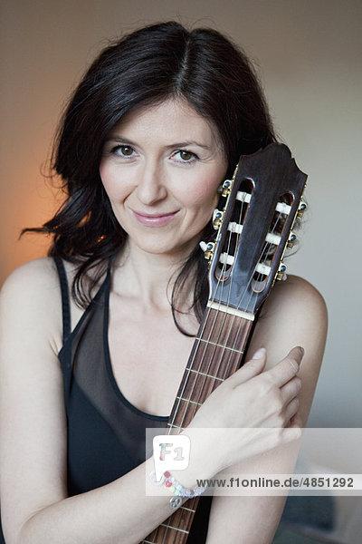 Frau  die eine Gitarre hält