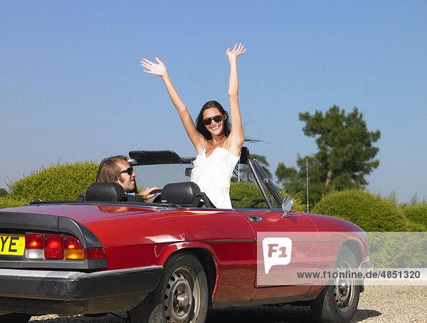 Frisch verheiratetes Paar im Auto  auf Wiedersehen.
