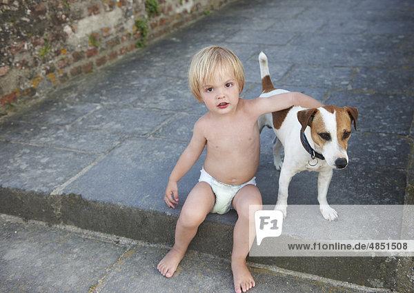Kleiner Junge spielt mit einem Hund Kleiner Junge spielt mit einem Hund
