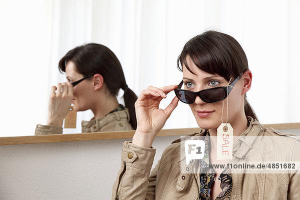 Frau beim Anprobieren der Sonnenbrille