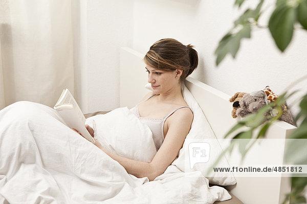 Junge Frau im Bett  lesend