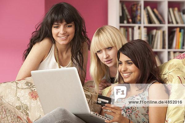 Drei junge Frauen beim Einkaufen am Computer