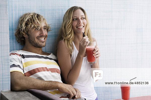 Kerl und Mädchen lachend mit roten Smoothies