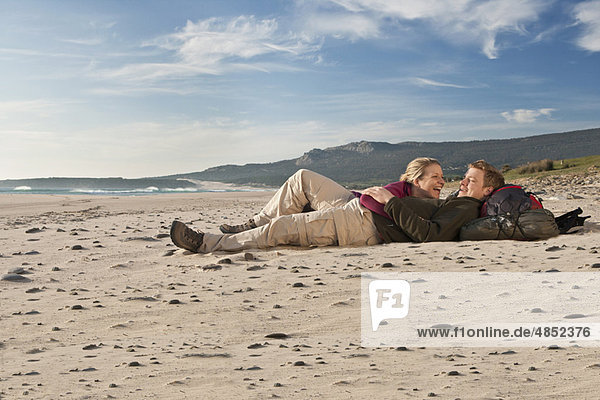 Junge Rucksacktouristen am Strand liegend