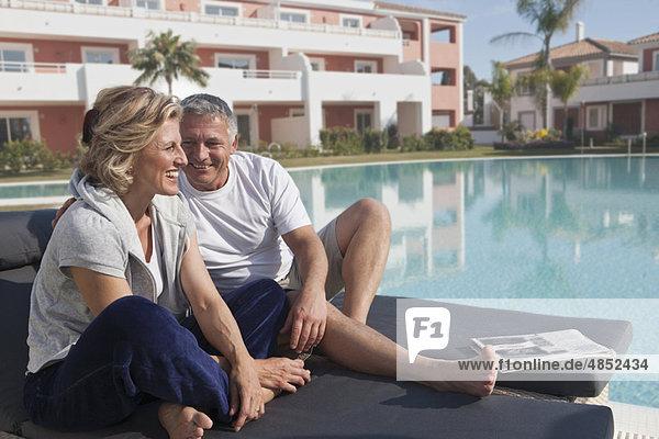 Reife Paare auf Solarien am Pool