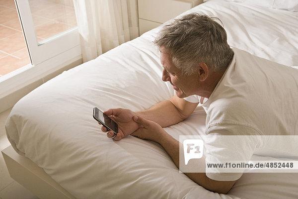 Reifer Mann im Bett mit Smartphone