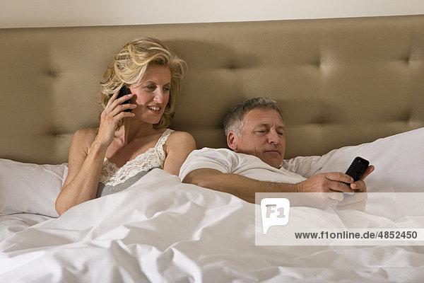 Reife Paare im Bett mit Smartphones