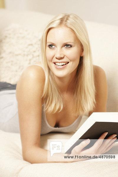 Blonde junge Frau liest ein Buch auf der Couch
