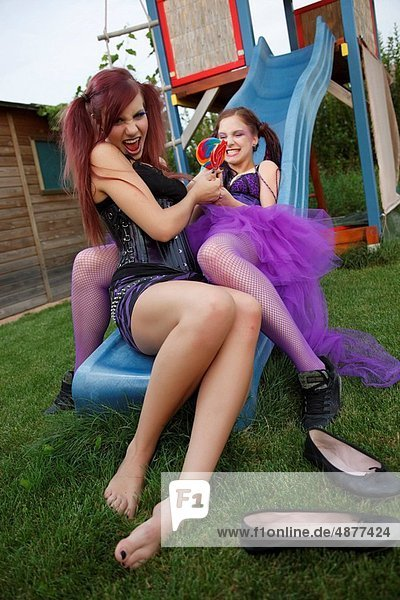 two girls with lolly on slide