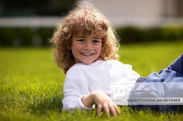 smiling curly haired boy resting in the grass