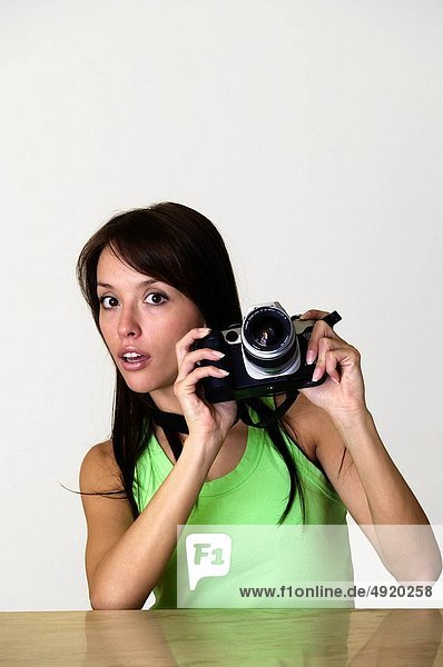 astonished young female photographer looking away from her camera