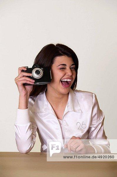 female photographer flirting while holding a camera