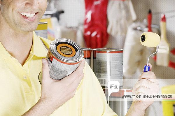 Mann  hält ein Paint kann in einem Hardware-Speicher Mann, hält ein Paint kann in einem Hardware-Speicher