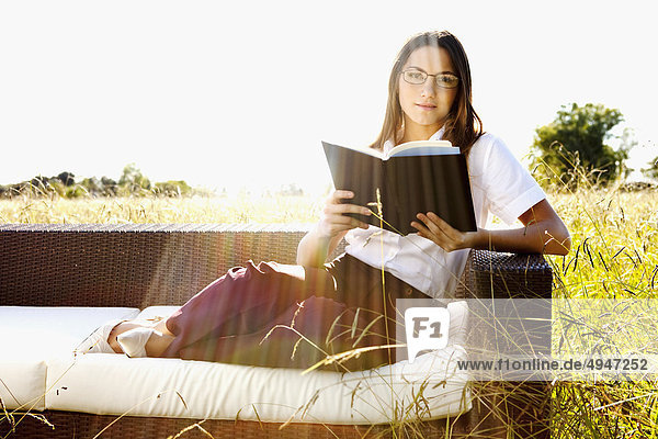 Businesswoman reading a book on a sofa in a grassland