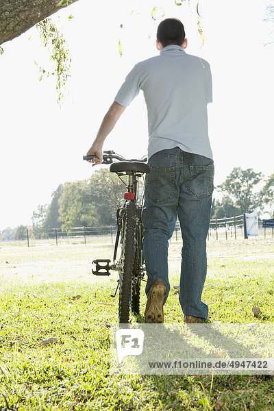 Man with a bicycle in a park