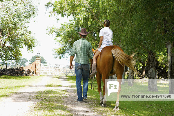 Frau mit einem Mann führt das Pferd Reiten Frau mit einem Mann führt das Pferd Reiten