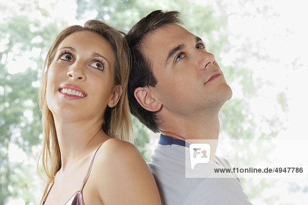 Paar Rücken an Rücken sitzen und lächelnd
