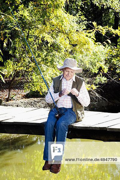 Man sitzt auf einer Promenade und die Vorbereitung für Fischerei