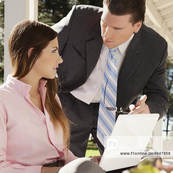 Teenagerin mit einem Laptop mit einem Mann neben ihr stehen