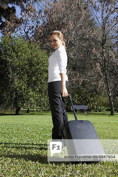 Geschäftsfrau ziehen einen Koffer in einem park