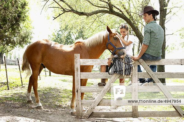 Paar mit einem Pferd auf einer ranch Paar mit einem Pferd auf einer ranch