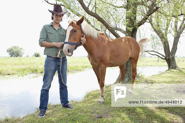 Cowboy stehen in der Nähe ein Pferd in einer farm