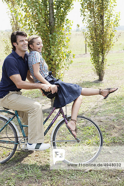 Couple riding a bicycle in a park