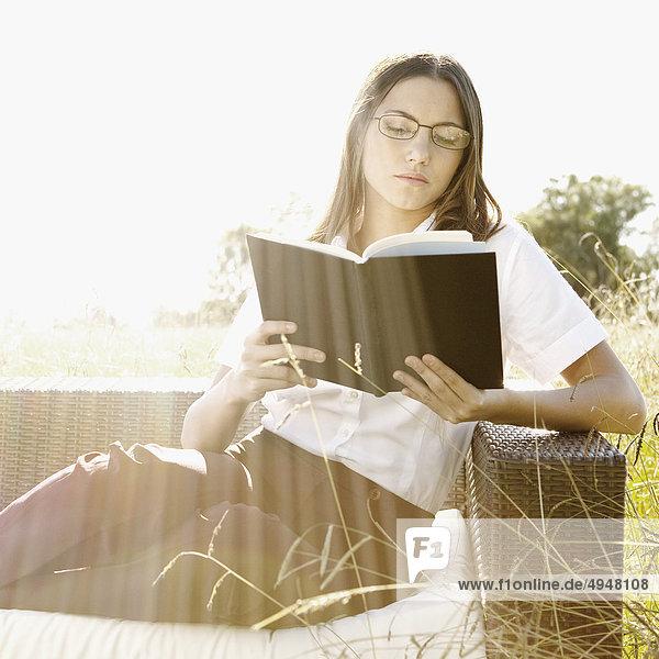 Geschäftsfrau Couch Buch Wiese Taschenbuch vorlesen