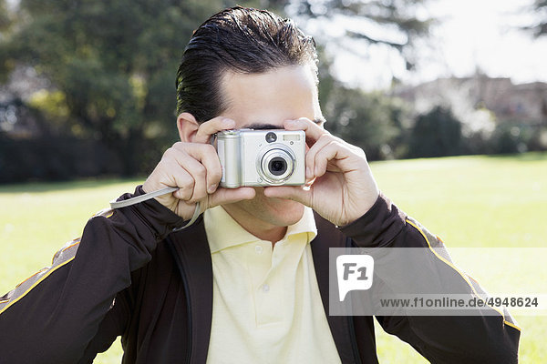Man taking a picture with a digital camera in a park