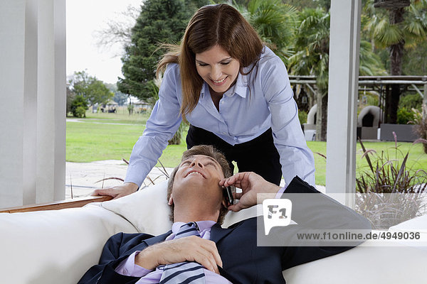 Businessman talking on a mobile phone and looking at a businesswoman