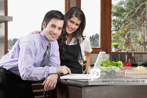 Porträt von einem Paar mit einem Laptop in der Küche