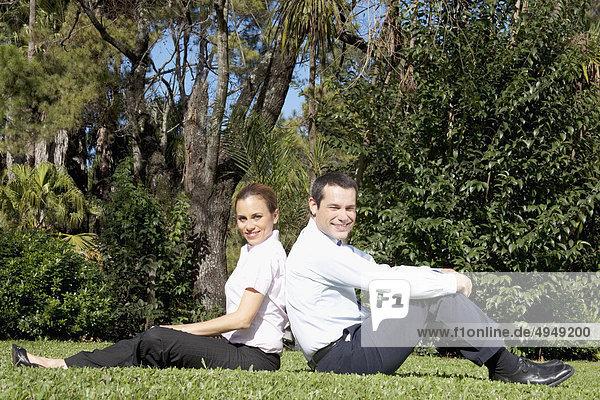 zwei Geschäftsleute Sitting wieder in einem park
