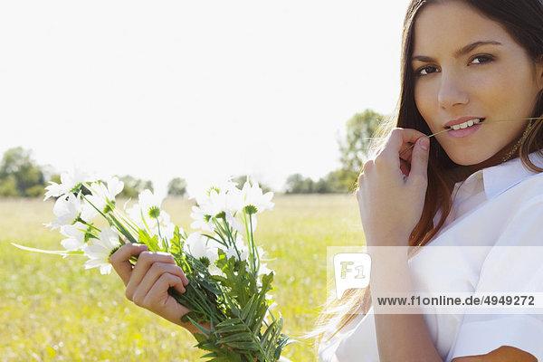 Teenage Mädchen hält einen Blumenstrauß in einem Feld