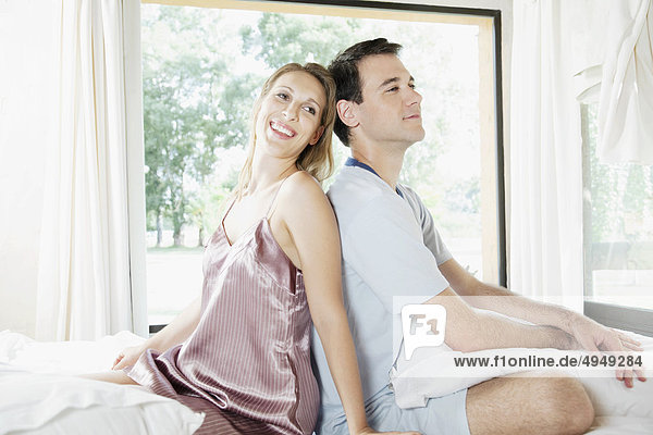 Couple sitting back to back on the bed and smiling