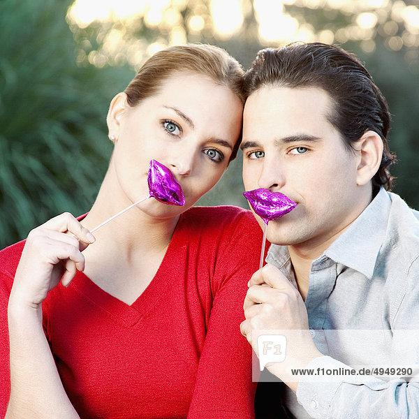 Paar hält Lip Form Spielzeug an ihre Lippen mund Paar hält Lip Form Spielzeug an ihre Lippen,mund