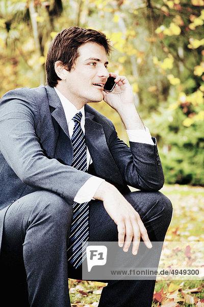 Kaufmann sprechen auf einem Mobiltelefon in einem park Kaufmann sprechen auf einem Mobiltelefon in einem park