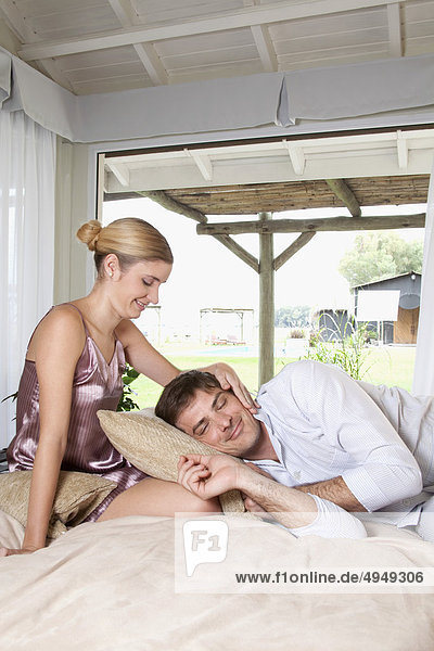 Mann liegt in seiner Frau Runde auf dem Bett