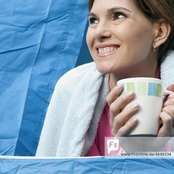 Frau trinkt eine Tasse Kaffee in einem Zelt Frau trinkt eine Tasse Kaffee in einem Zelt