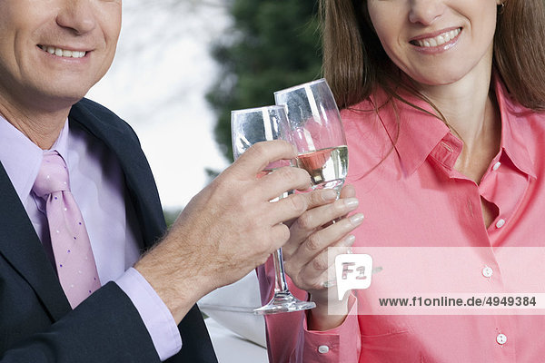 Kaufmann und eine geschäftsfrau toasting with champagne
