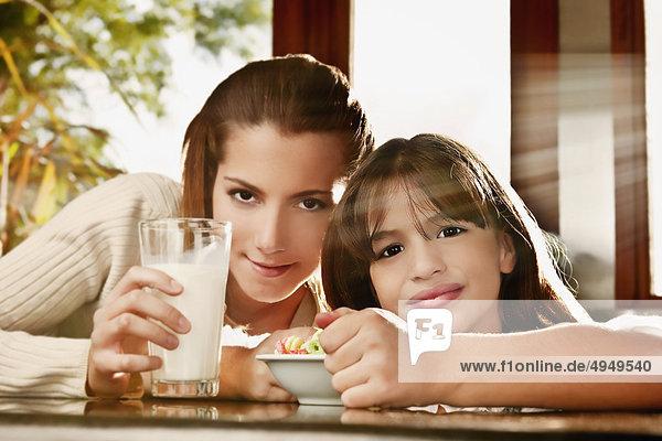 Mädchen und ihre Mutter mit einem Glas Milch und Getreide