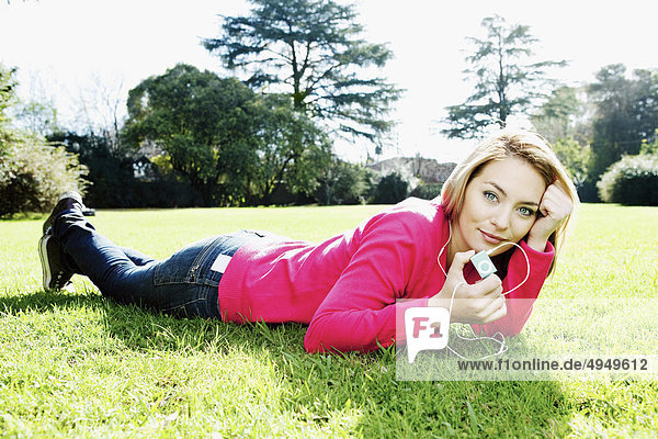 Woman lying in a park and listening to an MP3 player