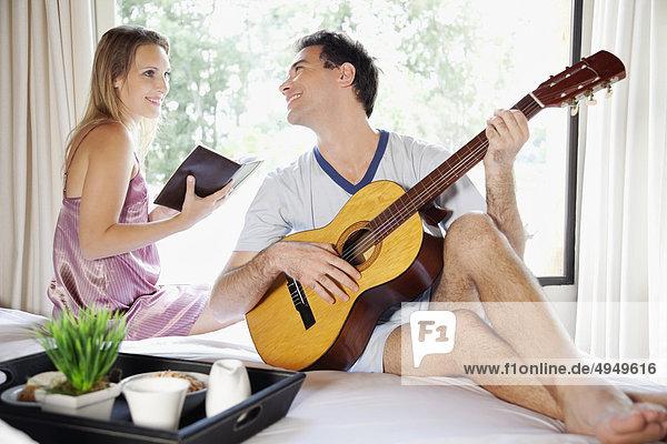 Mann Ehefrau Buch halten Bett Gitarre Taschenbuch spielen Mann,Ehefrau,Buch,halten,Bett,Gitarre,Taschenbuch,spielen
